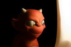 调查光的红魔小雕象 在黑色 免版税库存图片