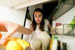 调查冰箱的妇女 免版税库存照片