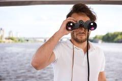 调查双筒望远镜的年轻人 库存图片