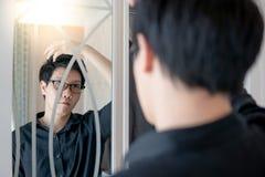 调查在壁橱的镜子的亚裔人 库存照片