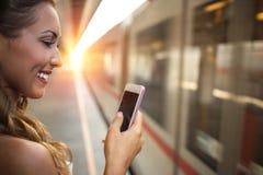 调查她的智能手机的美丽的少妇 库存照片