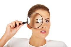 调查放大器的女实业家和有一只大眼睛 库存图片