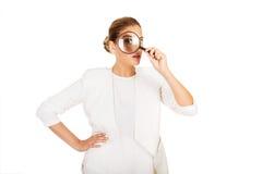 调查放大器的女实业家和有一只大眼睛 免版税库存图片