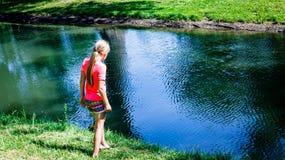 调查池塘的小女孩 免版税库存照片