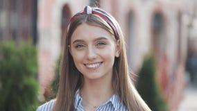 调查照相机和微笑的身分的一美丽的年轻女人的画象在老街道背景 ?? 股票视频