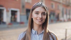 调查照相机和微笑的身分的一美丽的年轻女人的画象在老街道背景 ?? 影视素材
