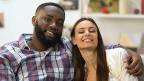 调查照相机和拥抱在沙发的美好的mixed-race夫妇开会 股票录像