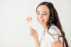 调查照相机和拿着棒棒糖的逗人喜爱的少妇 正的情感 免版税库存图片