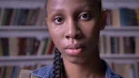 调查照相机和身分的年轻非裔美国人的女学生在图书馆里,严肃和关心