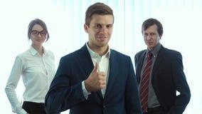 调查照相机的三个成功的商人队  显示伟大的大手指  股票录像