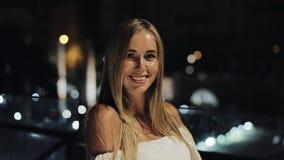 调查照相机的可爱的愉快的女孩 一个美丽的少妇的画象在晚上在城市,慢动作 股票录像