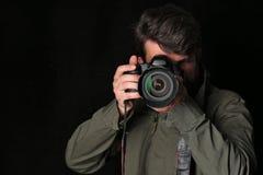 调查照相机的摄影师拍照片 关闭 黑色背景 库存图片