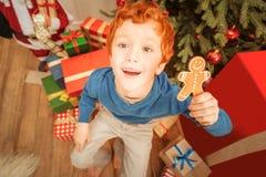 调查照相机的激动的姜孩子,当拿着姜饼人时 免版税库存照片