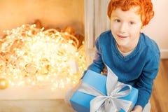 调查照相机的迷人的孩子,当拿着礼物时 免版税库存照片