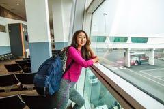 调查窗口的年轻俏丽的妇女在等待她的飞行的机场 免版税库存照片