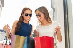 调查购物袋的愉快的妇女户外 免版税图库摄影