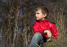 调查距离的夹克的男孩 免版税图库摄影