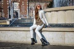 调查距离的妇女,当坐在喷泉附近在米兰时 免版税库存图片