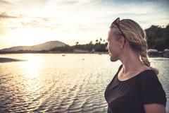 调查距离的热带海滩的少妇在与拷贝空间的美好的日落期间 库存图片