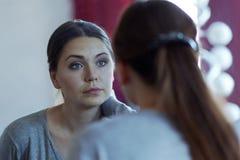 调查镜子的一名年轻可爱的白种人妇女的反射 佩带偶然,美丽的蓝眼睛,严肃的神色 免版税库存图片