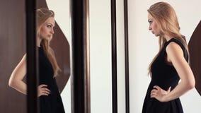 调查镜子的年轻可爱的白肤金发的快乐的女孩,准备好 影视素材
