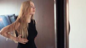 调查镜子的年轻可爱的白肤金发的快乐的妇女,准备好 影视素材