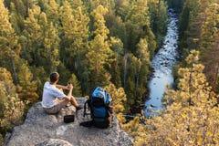调查从山峰的距离的背包徒步旅行者 免版税库存图片