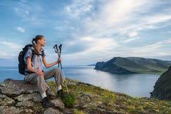 调查从山峰的距离的年轻背包徒步旅行者 免版税库存照片