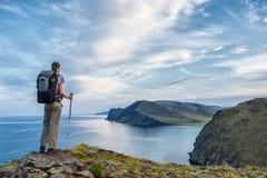 调查从山峰的距离的年轻背包徒步旅行者 图库摄影