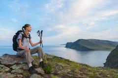 调查从山峰的距离的年轻背包徒步旅行者 库存照片