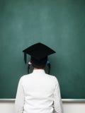 调查黑板的年轻女性书呆子 免版税库存图片