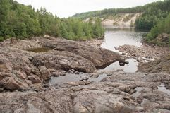 调查camerarocky河床的灰色猫和古老绝种火山和喷泉在卡累利阿 免版税图库摄影