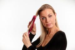 调直她的头发的美丽的白肤金发的妇女 免版税库存照片