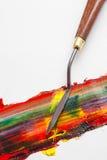 调色刀和混杂的油漆在白色帆布 免版税图库摄影