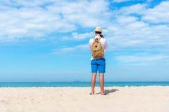 调遣结构树 拿着照相机为的愉快的微笑的白种人旅游亚裔年轻人在海滩拍照片登记 免版税库存图片