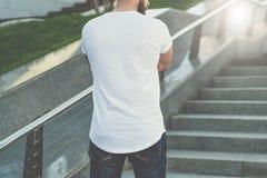 调遣结构树 查出的背面图白色 在白色T恤杉打扮的有胡子的行家人是在步的立场 在背景是草坪 嘲笑 库存图片