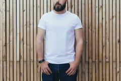 调遣结构树 正面图 在白色T恤杉打扮的年轻有胡子的行家人是室外的立场反对木墙壁 嘲笑 库存照片
