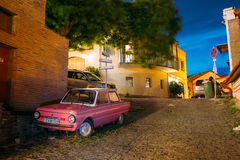 调整在被铺的街道上的停放的稀有桃红色微型车Zaporozhets  免版税库存图片