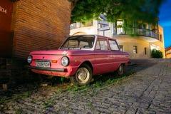 调整在被铺的街道上的停放的稀有桃红色微型车Zaporozhets  图库摄影