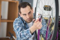 调整在轮子的年轻自行车技术员光芒 库存照片