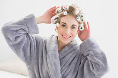 调整她的卷发夹的微笑的轻松的白肤金发的妇女 免版税图库摄影
