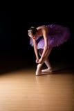 调整她的鞋子的年轻女性芭蕾舞女演员 免版税库存照片