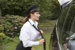 调整她的领带的专业母汽车司机 免版税库存照片