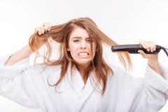 调直她的头发的恼怒的被激怒的少妇使用直挺器 免版税库存照片