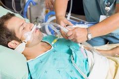 调整气管内管住院病人的护士 免版税库存图片