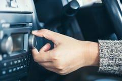 调整汽车收音机的音量妇女手 免版税图库摄影