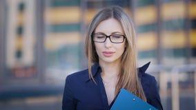 调整玻璃的女性办公室工作者 看照相机和调整玻璃的年轻成功的办公室职业妇女 影视素材