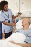 调整男性患者的IV滴水的护士在医院 免版税库存照片