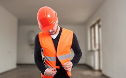 调整他的保护背心的年轻男性建设者 免版税库存照片
