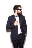 调整他的夹克和看在他的肩膀的英俊的年轻人佩带的太阳镜 免版税库存图片